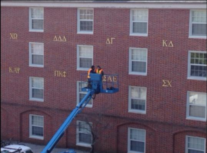 Furman employees take down SAE's letters off of the Lakeside Housing display of Greek life.
